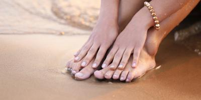hands touching feet at the beach