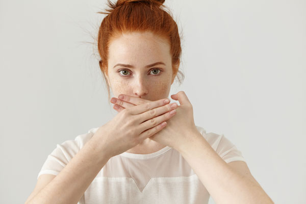 portrait-serious-young-ginger-european-woman-covering-mouth-with-both-hands-keeping-secret-freckled-redhead-female-blouse-doesn-t-want-spread-rumors-some-confidential-information